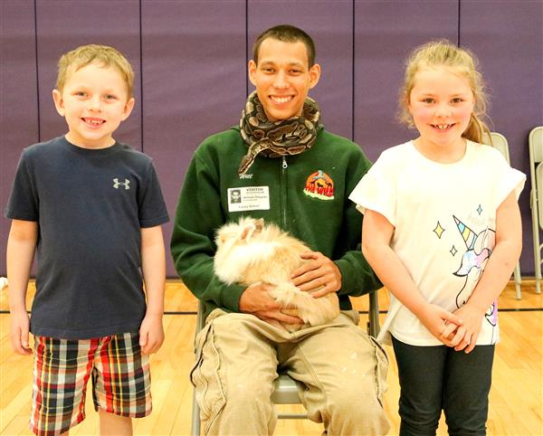 Jessie Sellin and Rhyan Schneider pose for a photo with zookeeper William Delgado