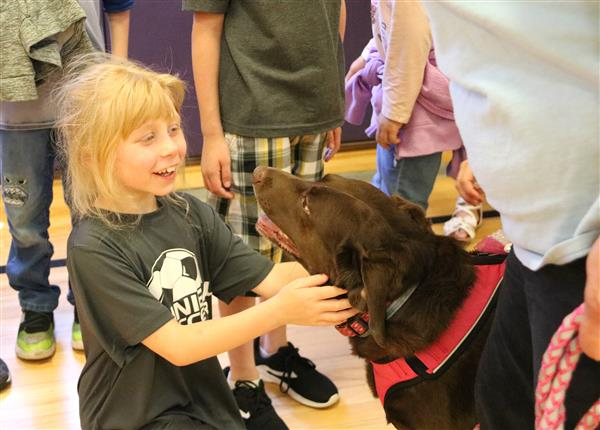Second-graders pet Harper, a lab mix who visited the school.